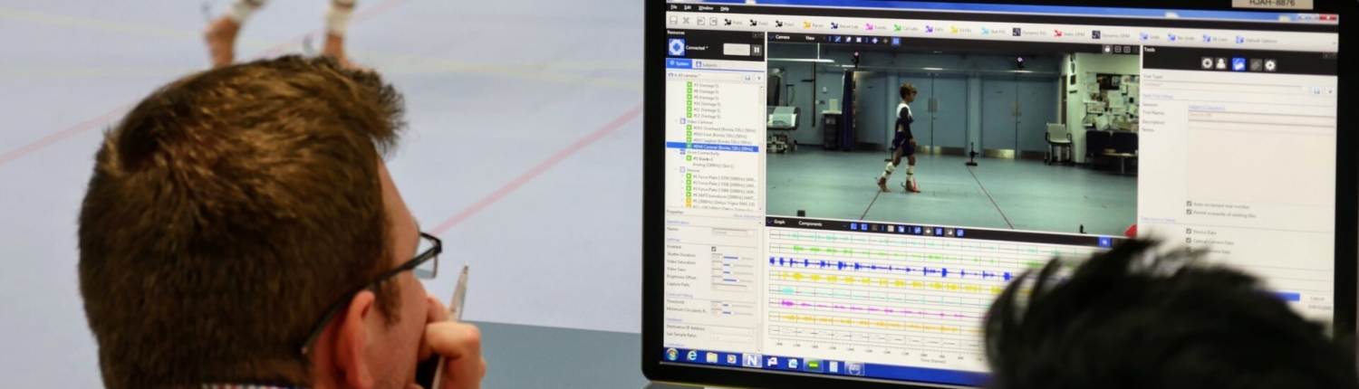 Researchers viewing computer screen of gait analysis session